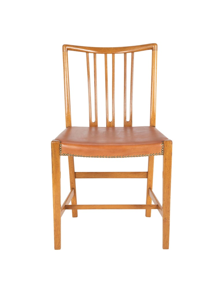 A set of 8 Hans Wegner bleached mahogany dining chairs with cognac leather seats with nail head trim. With mark to underside of apron.