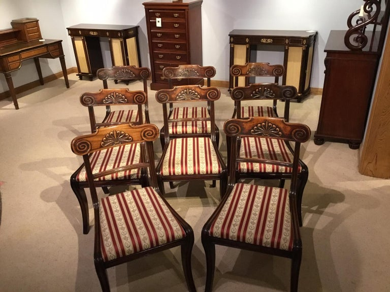 A set of 8 English mahogany Regency period antique dining chairs. Each having a broad solid mahogany top rail with carved anthemion detail, reeded supports, upholstered drop in seats and supported on sabre front legs with swept rear legs.