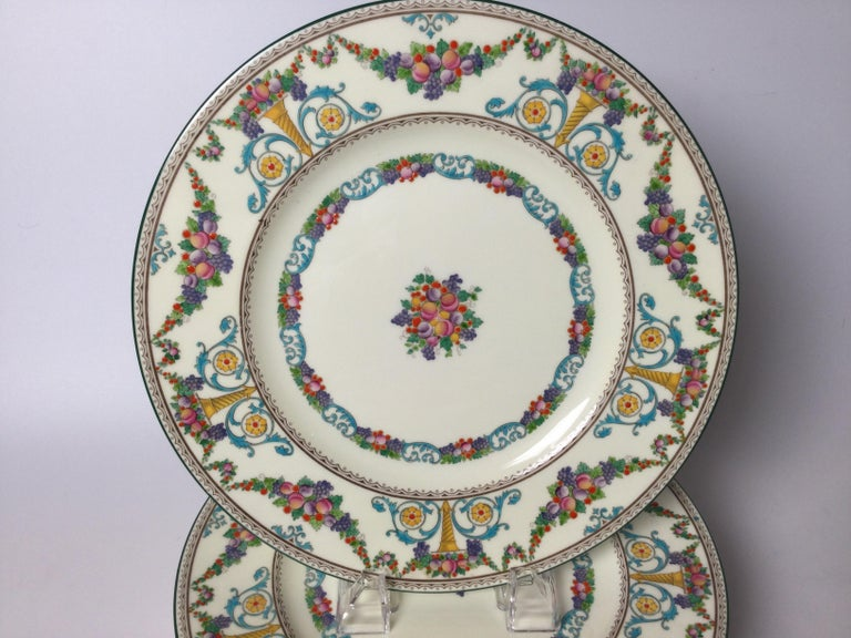 A set of 8 hand enameled service dinner plates. The vibrantly colored hand enameled and painted plates with garlands and uns of fuit a floral bouquets. England 1930s.