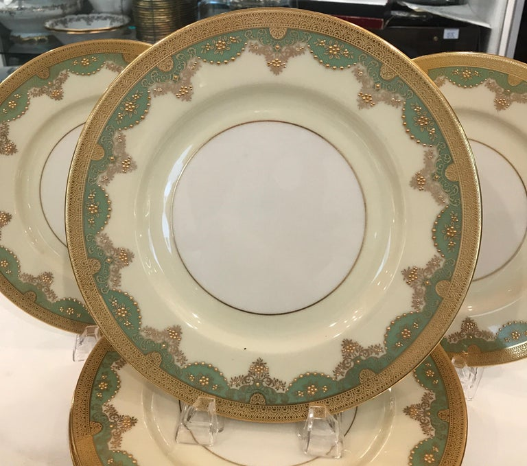 An elegant set of 12 raised gilt service dinner plates. The gold rims with a quince green highlighted with raised gilt beaded decoration. These plates with the pre 1930 Lenox green mark, Circa 1920...
