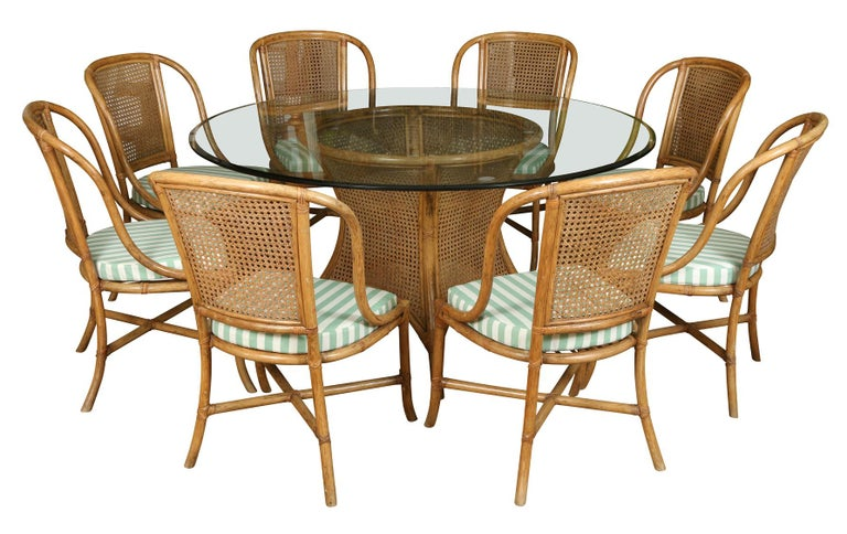 A chic set of rattan dining chairs with curved, caned backs and cross stretchers. The new custom removable seat cushions are in a cheerful green and white stripe.