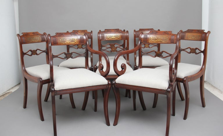 A set of eight Regency mahogany and brass inlaid sabre leg dining chairs, consisting of six side chairs and two armchairs, the shaped top rail carved and having a brass inlaid panel, wonderfully shaped and carved central rail, the armchairs having