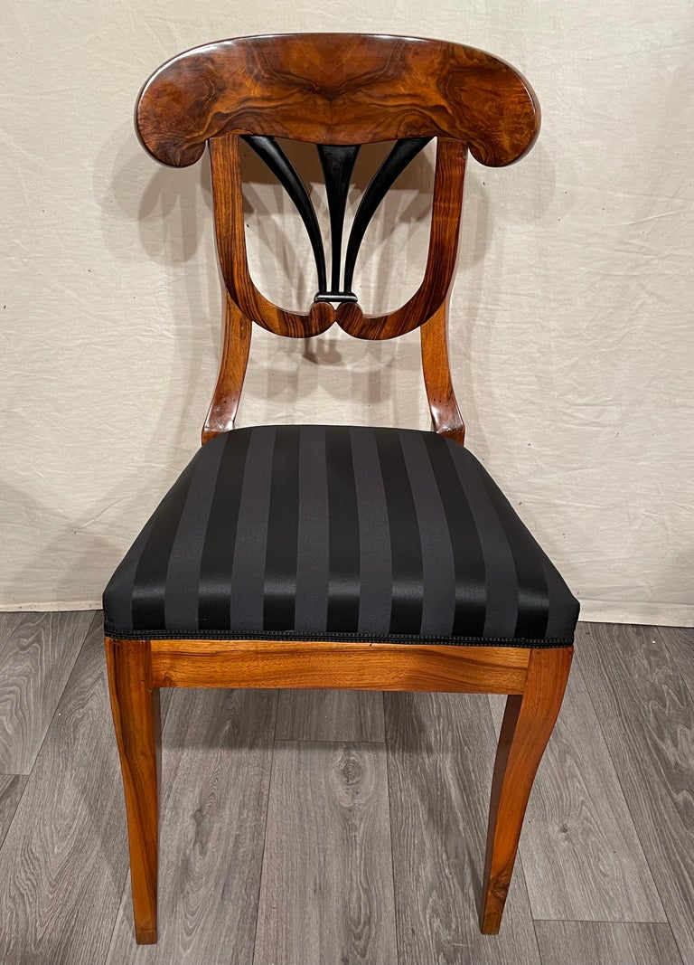 A set of four Biedermeier chairs, South Germany 1820. These very pretty unique Biedermeier chairs have a gorgeous walnut veneer. The open work back has ebonized details. The chairs are refinished and French polished and have a new upholstery and
