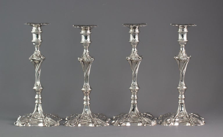 An exceptional set of four cast silver candlesticks, London, 1764-1765  An extremely fine set of four Georgian cast silver table candlesticks with leaf pattern decoration to the square shaped bases. A wrythen stem and leaf pattern and scroll form