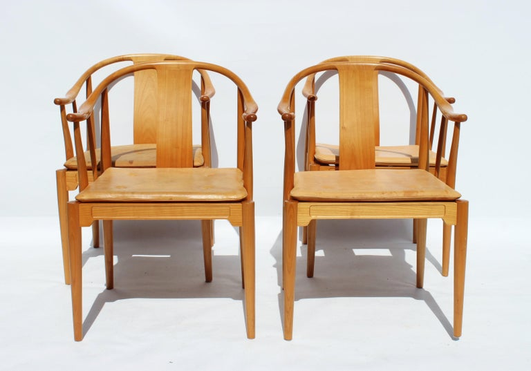 A set of four China chairs, model 4283, designed by Hans J. Wegner in 1944 and manufactured by Fritz Hansen in 1999. The chairs are of cherry and with cushion of patinated leather.
