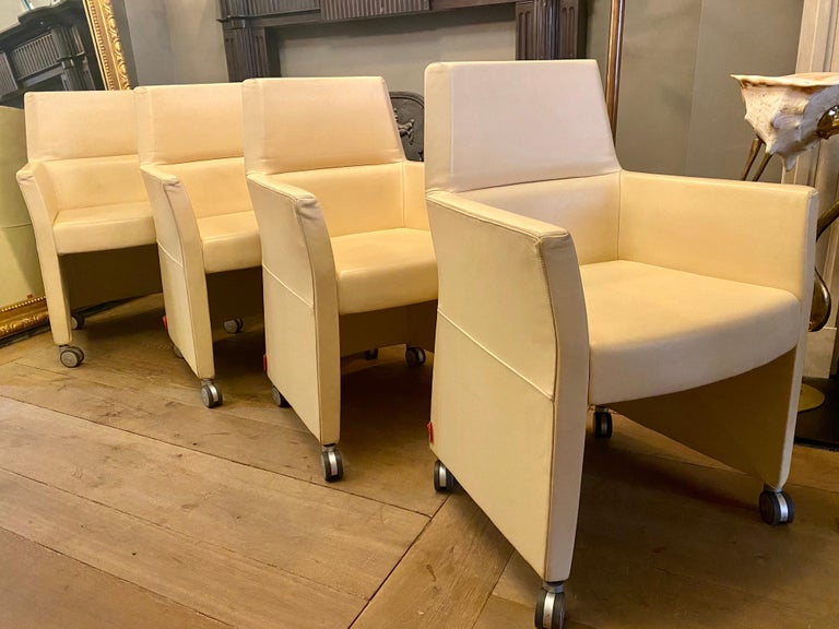A set of four of white leather chairs on castors by Enrico Pellizzoni. Versatile and comfortable can be used as dining chairs, luxury office chairs or occasional lounge chairs. Labelled and in good order.
