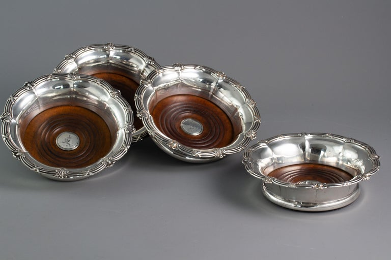 A very good set of four William IV silver wine coasters, of octagonal flared petal shaped form with a cast rim of ribbon and reed decoration and a shell at each node. The fruitwood bases with a central boss with the crest of a horned goat.  Marked