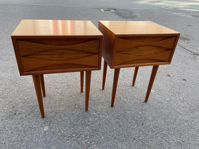 Mid Century-Modern teak cabinets by Niels Clausen for NC Mobler, Odense, Denmark. Produced c1960. Two drawers per cabinet with scalloped pulls and solid tapered legs.