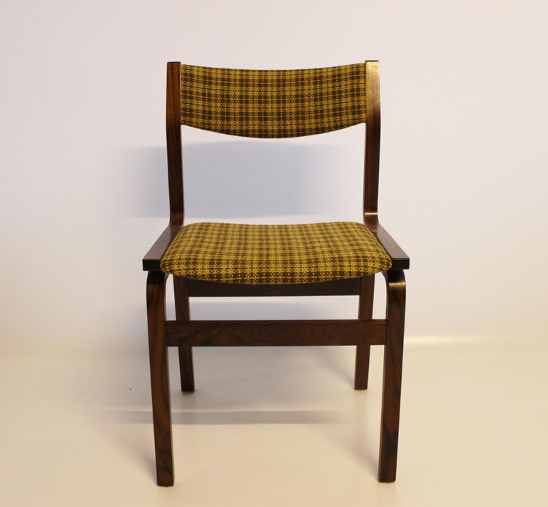 A set of six dining room chairs in rosewood and upholstered with yellow checkered fabric, of Danish design from the 1960s. The chairs are in great vintage condition.