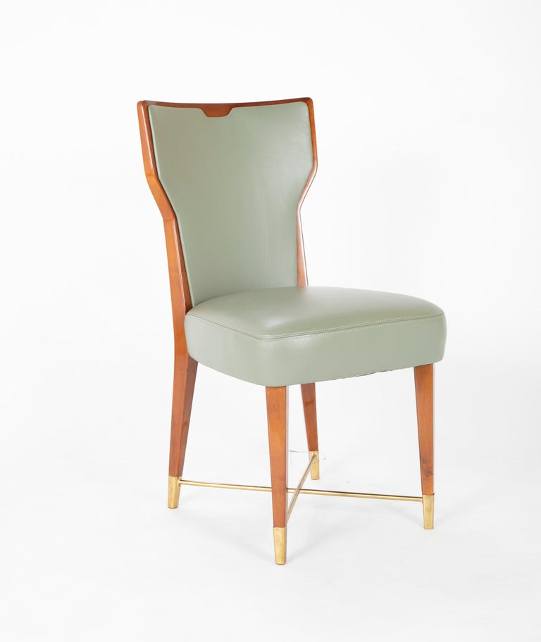 Giorgio Ramponi designed dining chairs. Leather covered mahogany with brass stretcher in a satin finish.   Literature- A similar model can be seen in Domus, July-August 1950, no. 248-49, back cover.