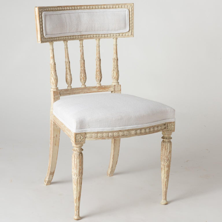 The backs on these elegant set of Gustavian Period chairs have spindles decorated with acanthus leaves, that end in a curved upholstered backrest. The acanthus motif is echoed on the legs as well. Chairs, such as these, are so comfortable that they