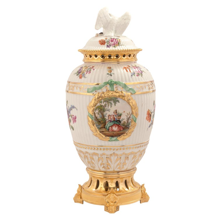 A fine and most charming complete set of three German 19th century porcelain and ormolu lidded urn garniture set. The central urn is raised by an elegant pierced ormolu base with fine foliate feet and a pierced and beaded rim. The body displays a