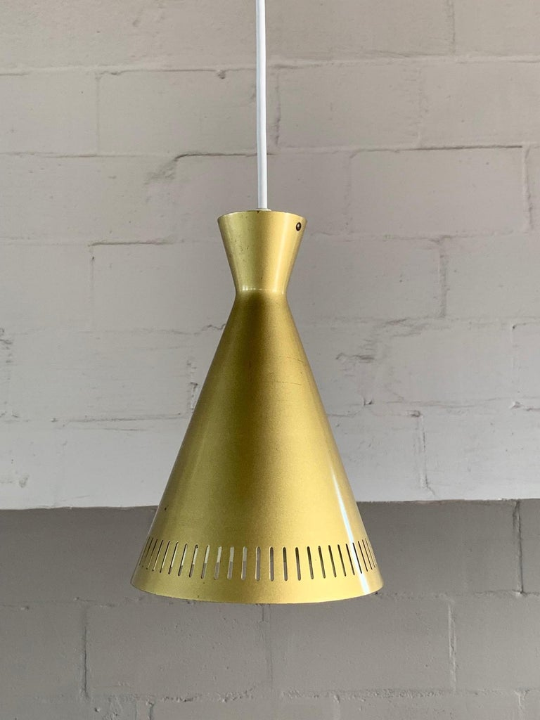 A set of three (3) unusual gold pendant lamps from, Germany, circa 1960s. Rewired for USA. The color is gold/chartreuse/olive. Measuring approximate 10