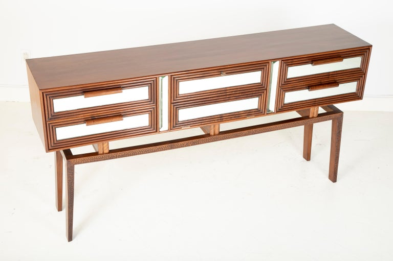 A labeled mirrored Mahogany sideboard designed by Silvio Cavatorta. Central panel opens to reveal a illuminated mirror lined bar. Facade of cabinet lined with faceted mirrors and reeded mahogany. Legs have scalloped carving into them. Label on back.