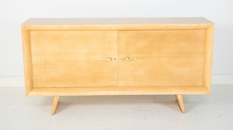 A maple credenza designed by Raymond Subes with light wood stringing inlay detail to doors.