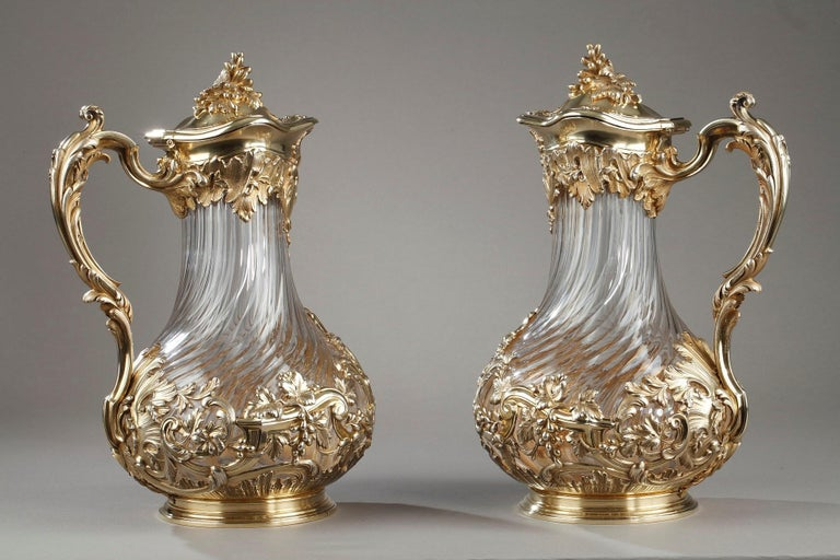 Important pair of carafes or jugs in orangeade in blown crystal, cut and twisted. The crystal is set in a silver and vermeil setting. The collar includes a cartouche decor, asymmetrical rocky patterns. The grip in high relief is adorned with a