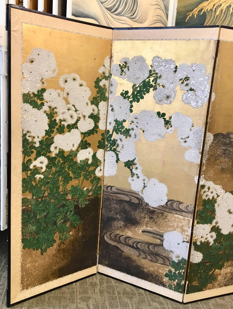 A beautiful six-panel early 19th century Japanese screen with raised gesso flowers and stylized stream, hand-painted on gold leaf.
