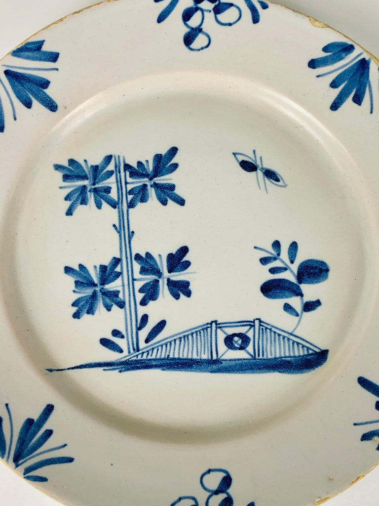 A small blue and white English Delft plate made circa 1740.  The hand-painted decoration is naive, showing a garden fence, a leafy tree, and a butterfly. On the border are leaves and flowers. The tin glaze is applied thinly, showing the underlying