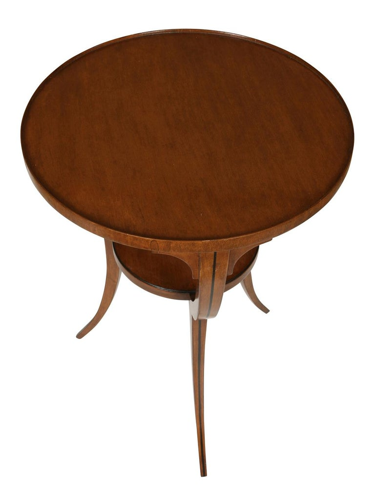 This sweet table can serve as a side table, nightstand, or a perch for drinks between two chairs. In walnut with lovely inlaid detailing, the table features a lower shelf and graceful saber legs.