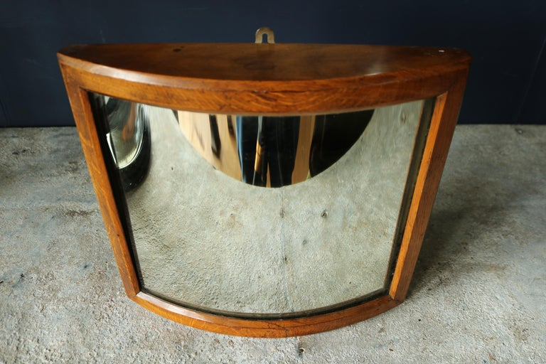 A late 19th century fairground mirror set in a beautiful golden oak frame with its original distortion mirror plate.