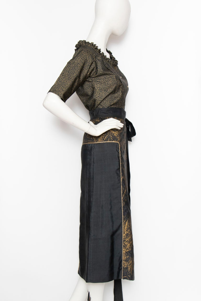 A 1980s Yves Saint Laurent Rive Gauche black and gold silk ensemble consisting of a short-sleeved blouse and wrap skirt. The blouse has a round neckline with small ruffle trim and a push-button front. The skirt has a gold paisley panel down the
