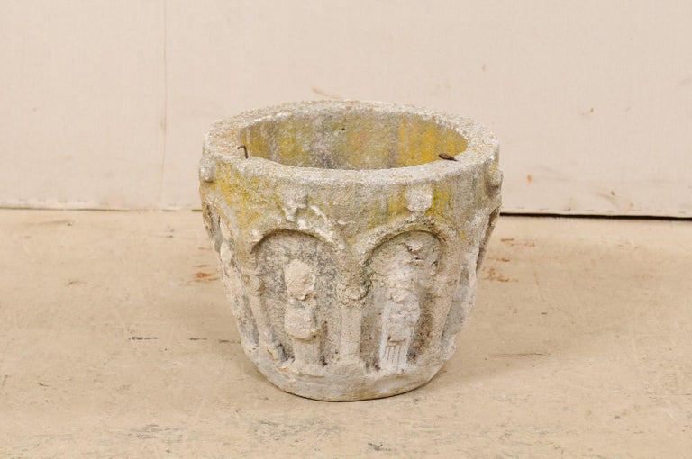 A Spanish cast-stone planter from the early 20th century. This antique planter from Spain was created from cast-stone and artfully decorated about the exterior with various archways and figures within. The round-shaped planter tapers gently and