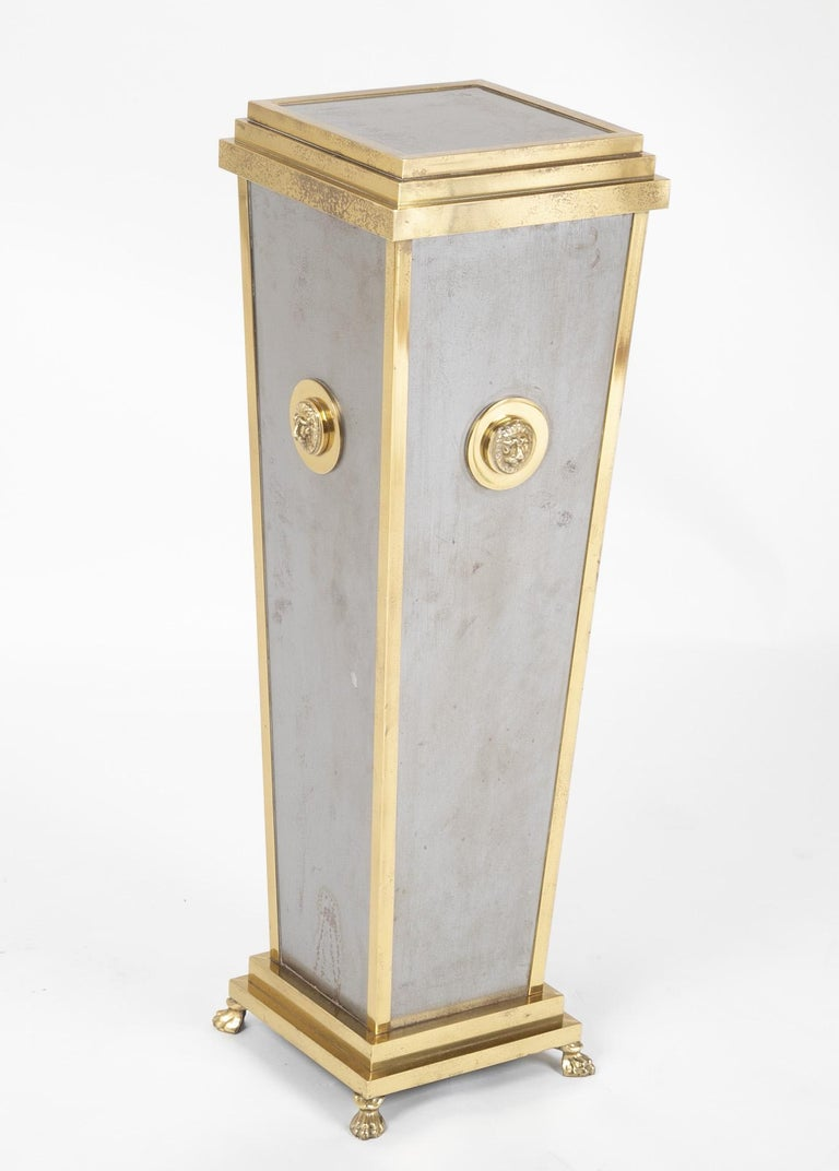 A Maison Jansen style brass and steel pedestal with Lion rosettes rising on paw feet.