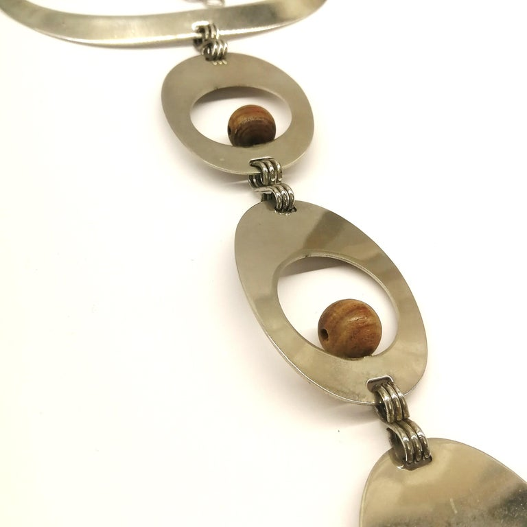A rare and wonderful chrome metal and walnut wood ball necklace, a long articulated pendant in ascendant size as it drops down the torso. As with all Pierre Cardin pendants from this period, the quality is excellent, and this is such a stylish and