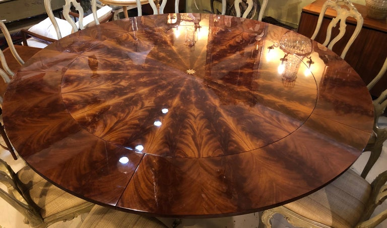 A  Georgian style flame mahogany sunburst inlaid circular dining table with five twelve inch leaves. Fully extended with all leaves this spectacular table is 87.5 inches in size. The strong and study table base having quad sprayed legs with brass