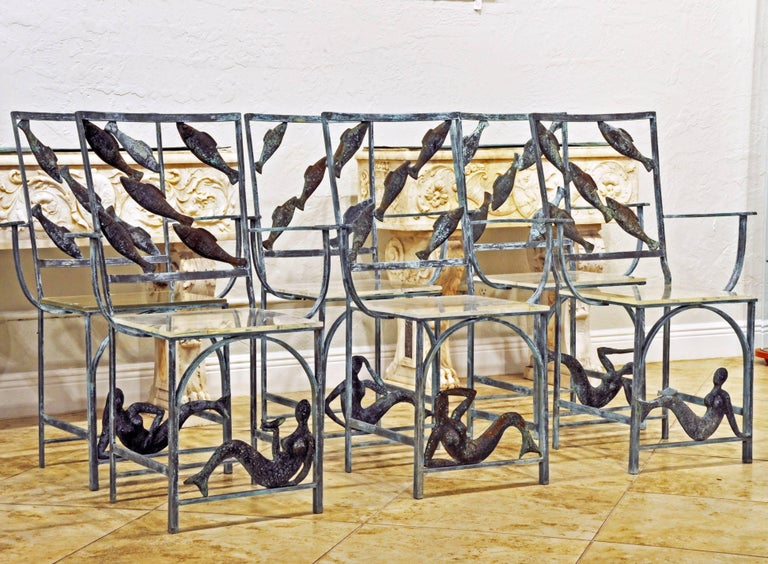 Made of solid weathered bronze and fitted with clear acrylic seats these chairs are different from anything we have ever seen. Their theme is the sea and they are adorned with swimming fish and gracious mermaids. Every chair slightly different when