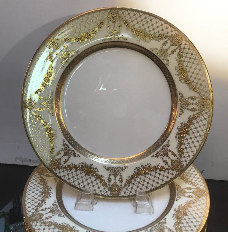 Elegant and graceful gilt service dinner plates with stunning gold encrusted border. The set was a custom pattern and in a lavish gold with slightly off white background. These plates will compliment almost any formal pattern in any color. The back