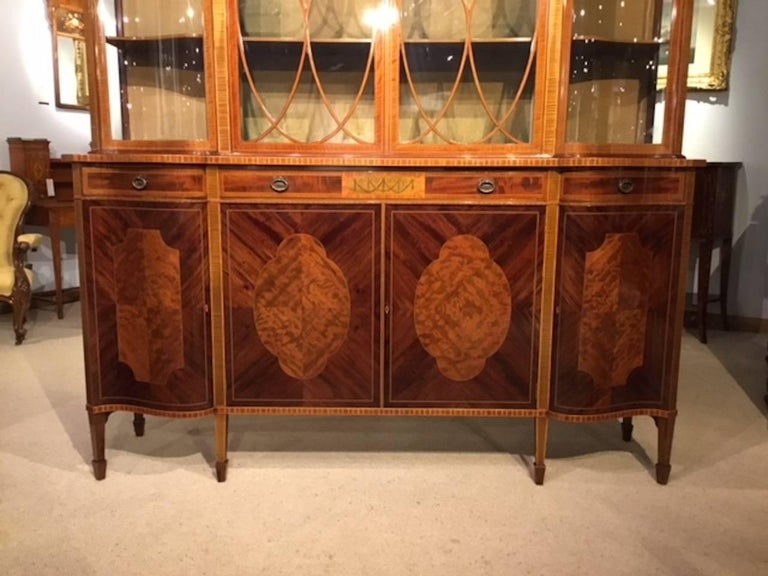 A superb quality large mahogany Edwardian Period antique display cabinet by Maple & Co of London. The upper section having serpentine ends and with a dentil inlaid cornice above a flame mahogany frieze and with a central marquetry inlaid panel. The