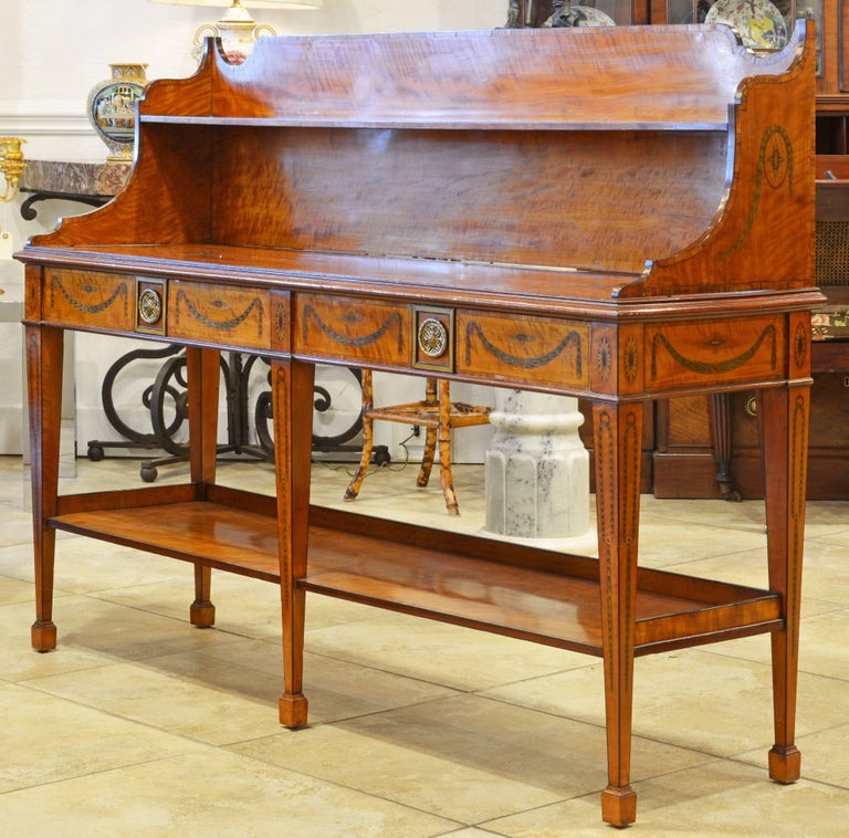 The incredible detail of the inlaid decorations with urns, garlands and sunbursts sets this exquisite piece of furniture apart. Fashioned in the Hepplewhite Adam style the server dated to the late 19th or early 20th century and is veneered with