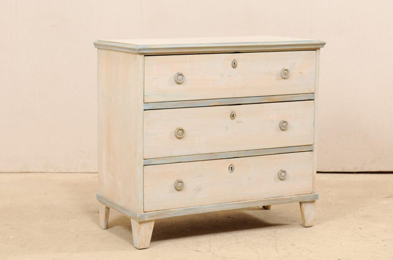 A Swedish Gustavian style painted wood chest from the mid-20th century. This vintage chest from Sweden, designed in typical Gustavian style, features a simple, clean design aesthetic. The rectangular-shaped top, with molded side trim, rests above a
