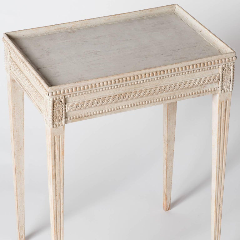 This elegant Gustavian style table has an intricate decorative design on the apron and ends in tapered reeded legs. The pale off-white paint surface is original.