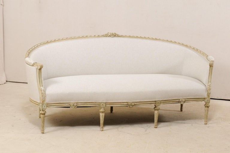 A Swedish late period Gustavian upholstered and wood sofa from the early to mid-19th century. This antique tub style sofa from Sweden features an elegantly arched top wooden top rail with carved rope trim and adorn in bunched floral carvings at the
