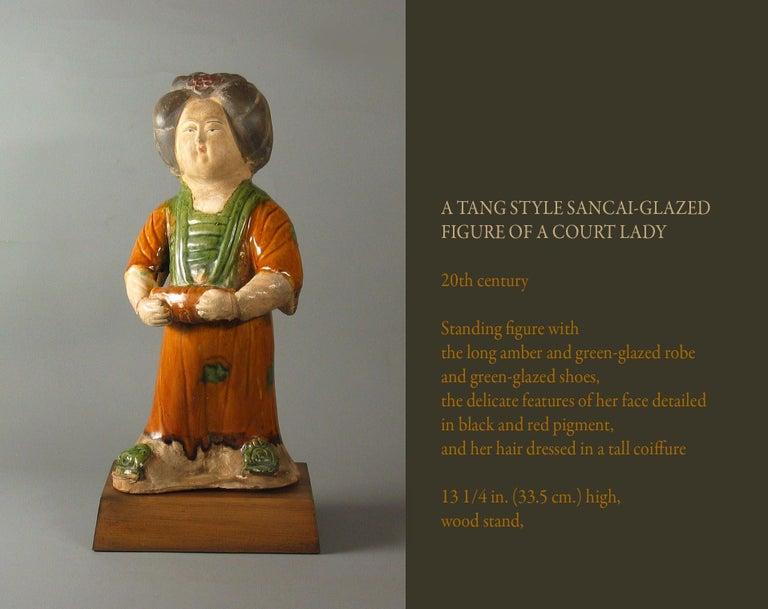 A Tang style Sancai-glazed Figure of a Court Lady,  20th century.  Standing figure with  the long amber and green-glazed robe  and green-glazed shoes,  the delicate features of her face detailed  in black and red pigment,  and her hair