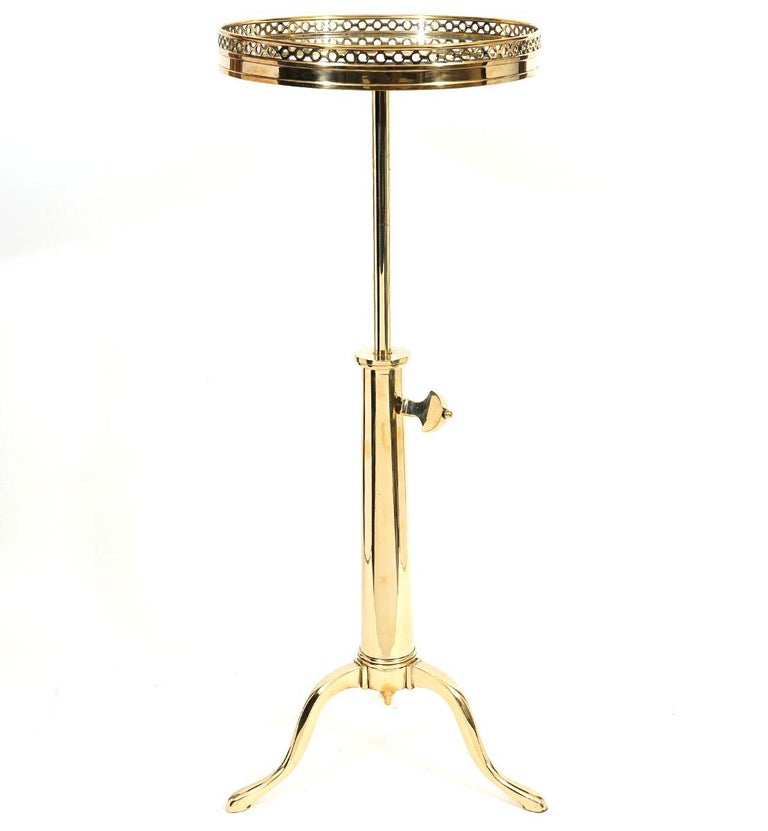 This French Maison Toulouse telescoping brass occasional tables, dating to around 1970 and retailed by John Boone NY, feature circular pierced gallery tops with inset mirror supported by an adjustable telescoping shaft and cabriole legs with pad