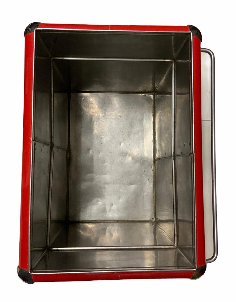 This a red large rectangular metal Coca Cola cooler with two handles. There is an upper compartment when you open the lid and below it, there is a large deep compartment for the Coca Cola sodas. A great piece for Coca Cola's collector. The Coca Cola
