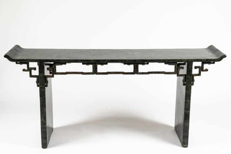 A chic and stylish altar style console table completely veneered in deep green marble. The details to the underside of the top are cast and patinated bronze. Table has style to spare and would work well in both a contemporary or traditional