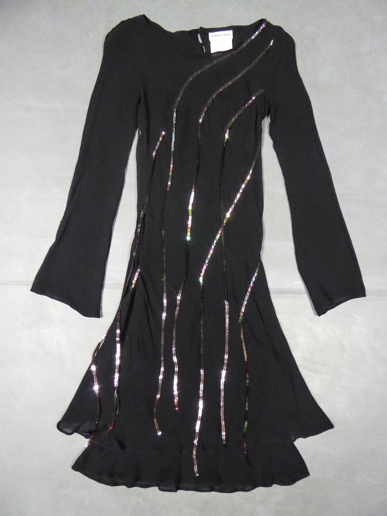 Circa 2000 France  Little Black Cocktail Dress in black silk crepe decorated with long iridescent sequined fringes by Thierry Mugler and dating from the 2000s. Short dress with round collarand long sleeves widened at the wrists. Appliqué fringes of