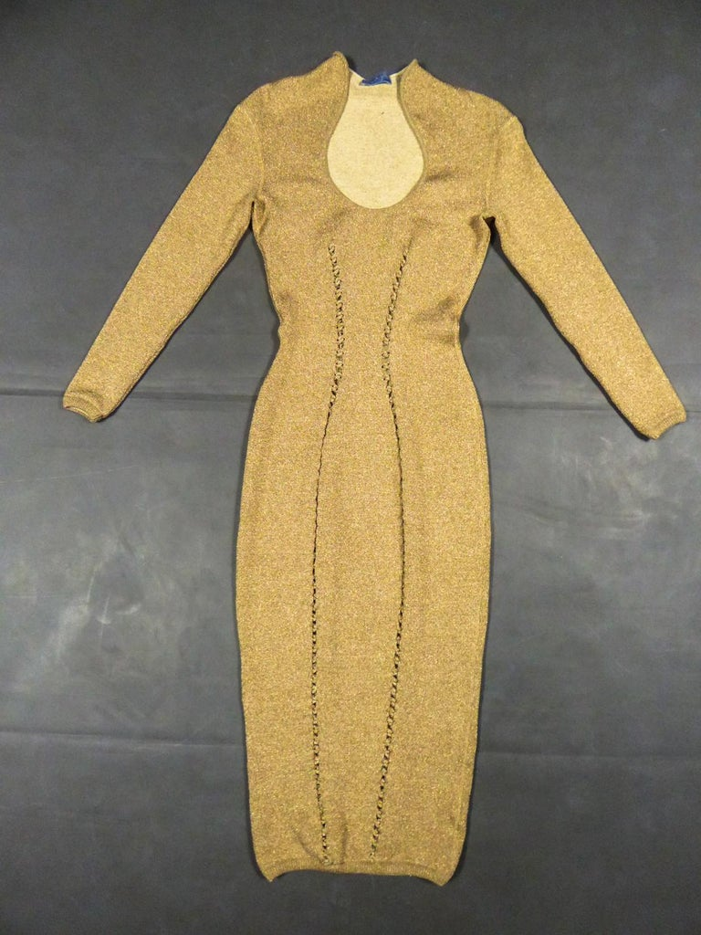 Circa 1990/2000 France  Long evening dress in golden lurex chiné knitwear and stretch cream woolby Thierry Mugler from the years 1990/2000. Stretch and skin-tight dress with plunging neckline, small turn up collar and long sleeves. Interlacing work