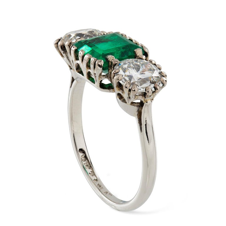 A three stone diamond and emerald ring, the rectangular-cut emerald weighing 1.79 carats, accompanied by GCS Report, stating to be of Colombian origin, set between two old-cut diamonds weighing 1.06 and 0.98 carats, all claw-set in platinum, circa