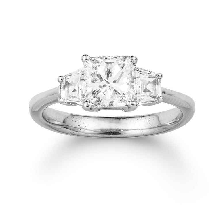 A three stone diamond ring, the centre a princess-cut diamond weighing 1.13 carats accompanied by GCS Report stating to be of H colour and VS1 clarity, claw-set between trapeze-cut diamond-set shoulders weighing a further total of 0.51 carats, to