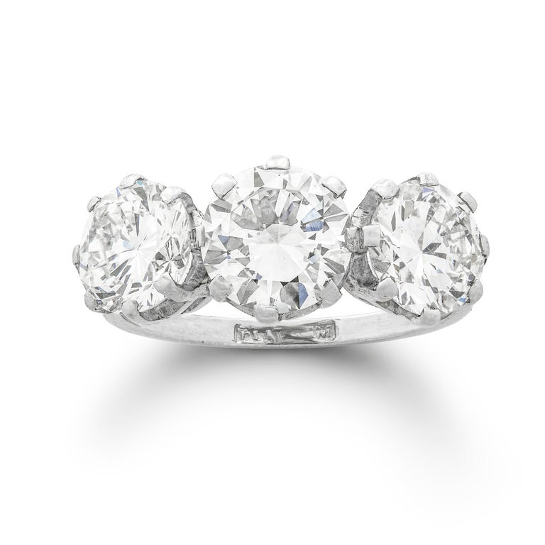 A three-stone diamond ring, the three round brilliant-cut diamonds weighing 1.51, 1.25 and 1.15 carats, respectively of  H, F and H colour, VS1, VS2 and I1 clarity,  certified AnchorCert , all claw-set in platinum to a D-section shank, hallmarked