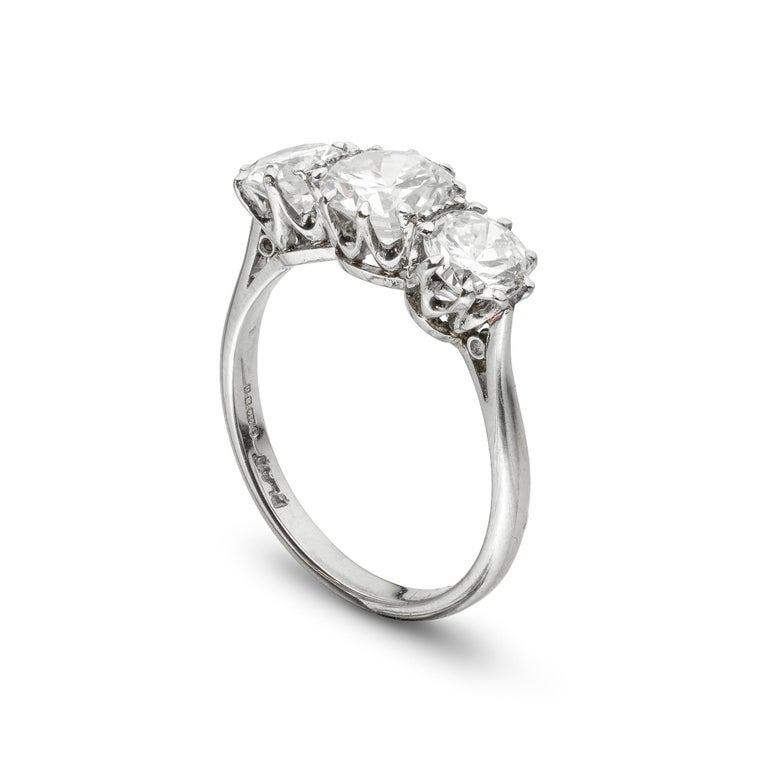 A three stone diamond ring, the central round brilliant-cut diamond weighing 0.92 carats, accompanied by GCS Report stating to be I colour, SI1 clarity, set between two round brilliant-cut diamonds weighing a further total of 1.08 carats, all
