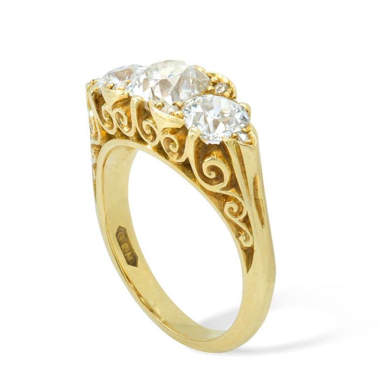 A three-stone diamond Victorian style ring, the central old-mine cut diamond weighing approximately 1 carat, flanked by four rose-cut diamond, all set between two round old European cut diamonds weighing approximately a further 0.8 carats in total,