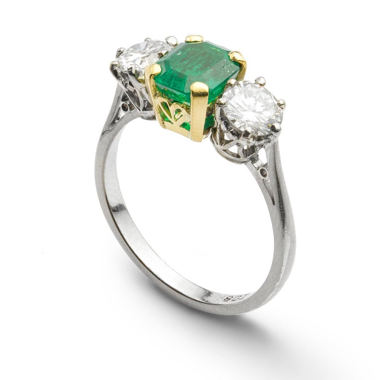 A three stone emerald and diamond ring, the central emerald-cut emerald, measuring approximately 7.0 x 6.2 x 4.2mm and weighing 1.34 carats, four claw set in gold, flanked by round brilliant-cut diamonds either side, weighing a total of 1.03 carats,