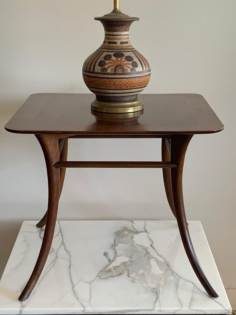 A classic table by T.H. Robsjohn-Gibbings for Widdicomb, circa 1950s with Klismos style legs. Made of walnut with beautiful graining, this is a side table or lamp table or just an occasional table that always finds use in modern or traditional