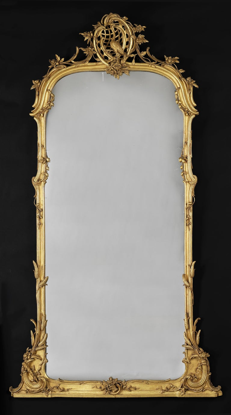 Avery fine carved giltwood mirror.  German, circa 1860.  The shaped moulded frame carved with wheat sheafs and entwined foliate forms, surmounted by an openwork rocaille cartouche centred by the figure of a Crane.